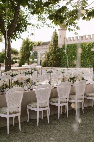 Outdoors wedding breakfast with white and pink flowers at Castell de Sant Marçal
