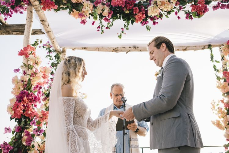 Boho Bride in Bardot Tulle and Lace Flora Bridal Wedding Dress and Groom in Grey Suit Saying Their Vows