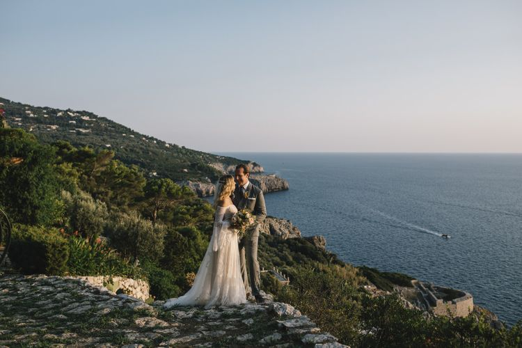 Coastal Portrait of Boho Bride in Bardot Tulle and Lace Flora Bridal Wedding Dress and Groom in Grey Ralph Lauren Suit