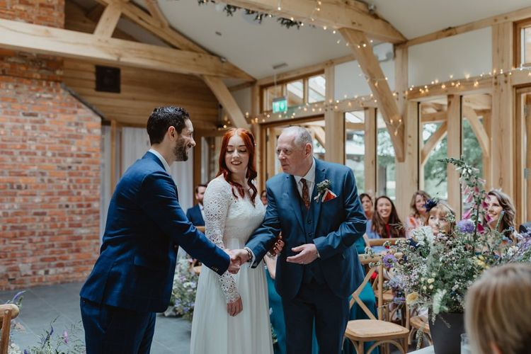 Groom Shakes Father Of Bride's Hand At Altar