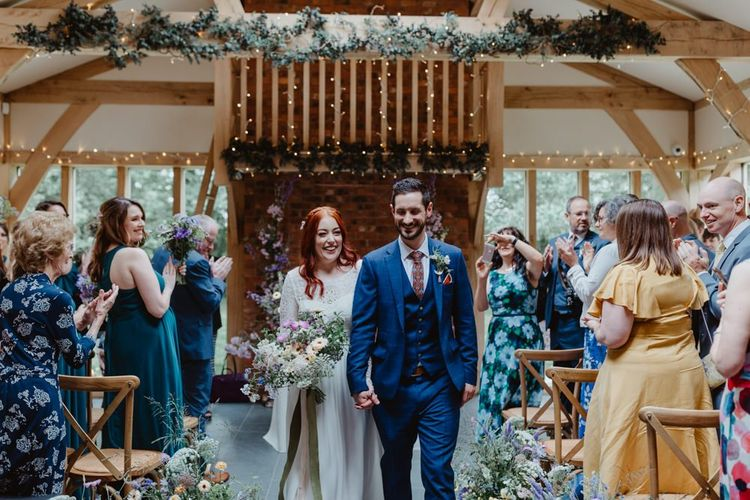 Bride and Groom Walk Back Up The Aisle After Saying I Do