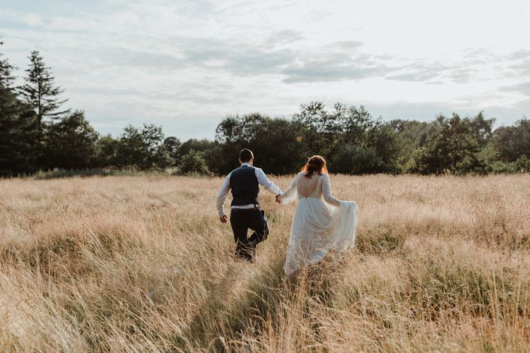 Bride and Groom Walk Through Meadow Holding Hands