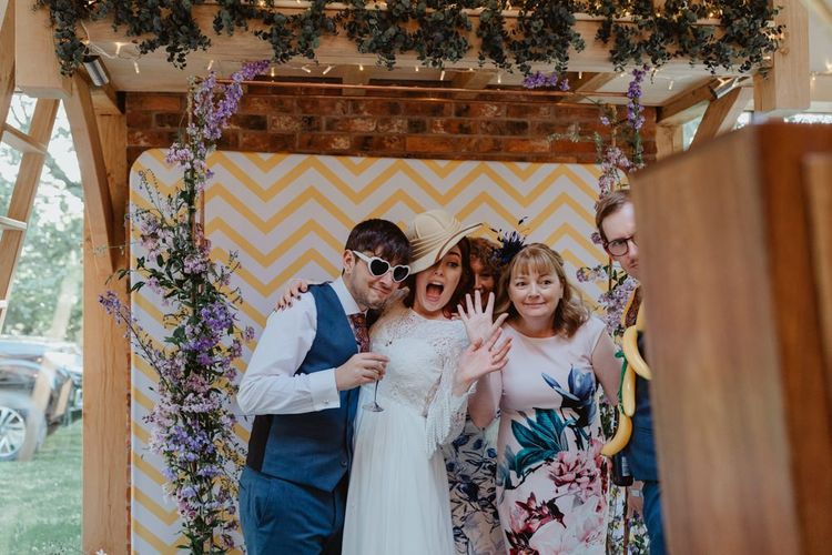 Bride and Guests Enjoy Photo Booth With Props
