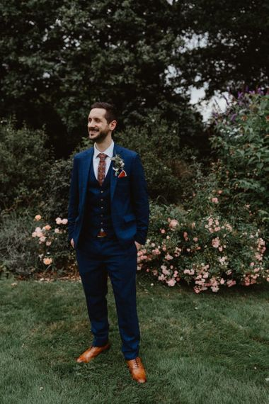 Groom In Navy Moss Bros Suit With Patterned Tie