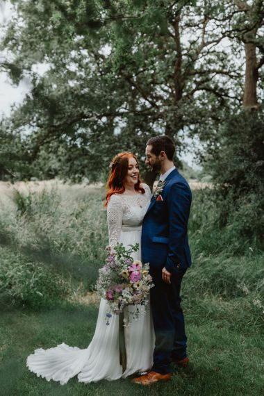 Bride and Groom Embrace In Meadows By Cheshire Wedding Venue