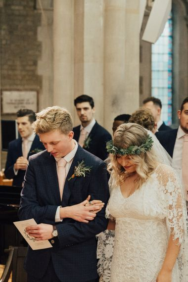 Bride in Grace Loves Lace Wedding Dress and Groom in Navy Suit Praying During Church Wedding Ceremony