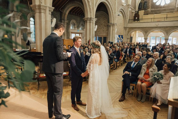 Bride in Grace loves Lace Wedding Dress with Long Sleeves and Groom in Navy Suit at the Altar Saying Their Vows