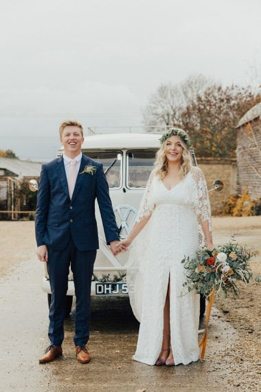 Boho Bride in Graces Loves Lace Wedding Dress and Groom in Navy Suit Holding Hands By their Camper Van Wedding Car