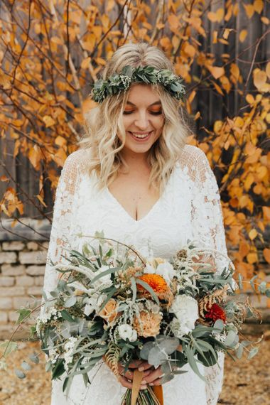 Boho Bride in Grace Loves Lace Wedding Dress and Foliage Flower Crown Holding an autumnal Bouquet