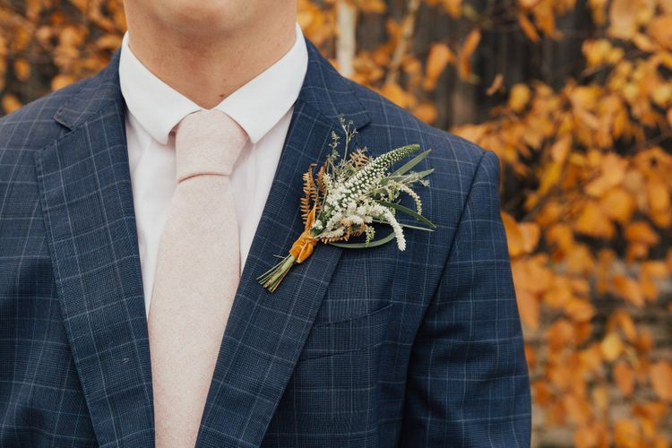 Groom in Navy Suit with Beige Tie and Orange and Green Buttonhole