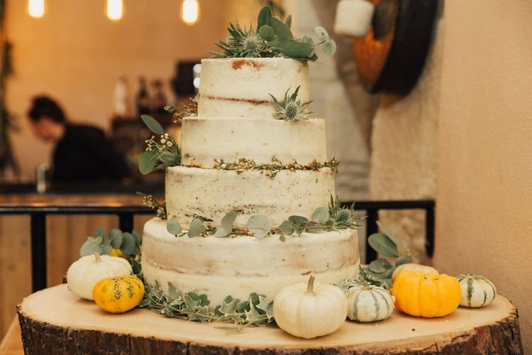 Semi Naked Wedding Cake on Tree Slice Decorated with Miniature Pumpkins and Foliage