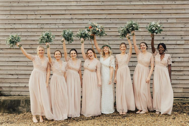 Bridal Party Portrait with Bride and Bridesmaids Waving Their Bouquets in the Air