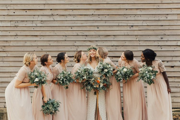 Bridal Party Portrait with Bridesmaids Giving the Bride a Kiss on the Cheek