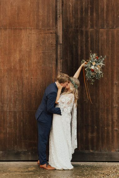 Bride in Grace Loves Lace Wedding Dress and Groom in Navy Suit Kissing