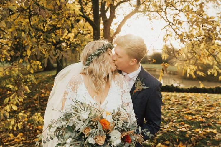 Autumnal Wedding Portrait with Bride and Groom Kissing During Golden Hour