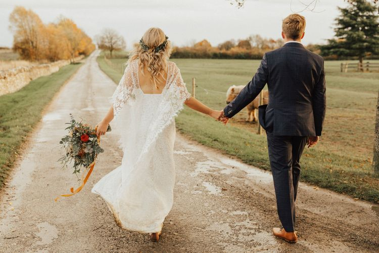 Groom in Navy Suit and Boho Bride in Grace Loves Lave Wedding Dress Holding Hands