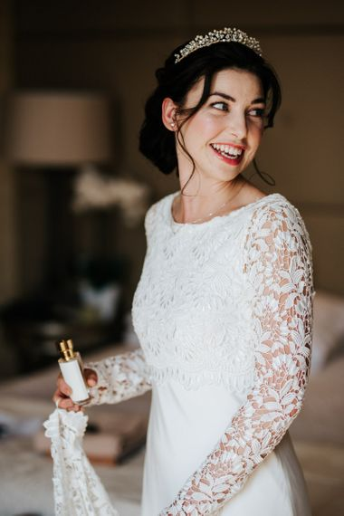 Bride turns and looks at herself in the mirror as she holds a small bottle of perfume