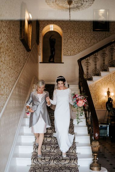 Mother of the bride and bride walk down the stairs of the petersham hotel in richmond and head towards wedding car
