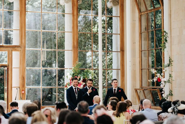Groom and two gromsmen stand at the front of the aisle at Nash Conservatory in Kew Gardens wedding waiting for the bride to arrive