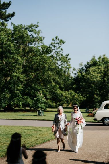 Bride walks towards her bridesmaids and flower girls waiting outside of the Nash Conservatory