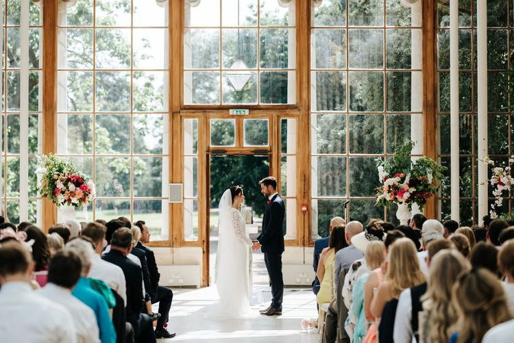 Bride and groom holding hands at the front of the aisle of Nash Conservatory at Kew Gardens