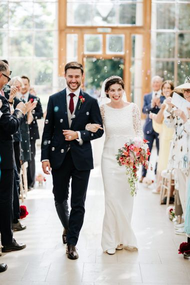 Bride and groom walk back down the aisle as a married couple while guests blow bubbles at them