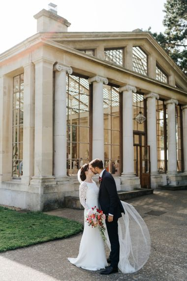 Bride and groom kiss outside of Nash Conservatory at Kew Gardens