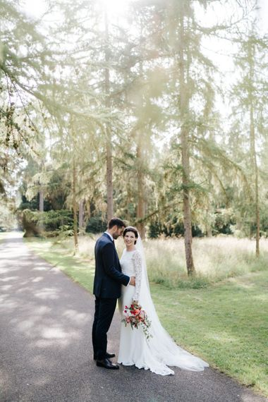 Bride and groom stand in beautiful light in Woodlands area in Kew Gardens and pose for a photograph