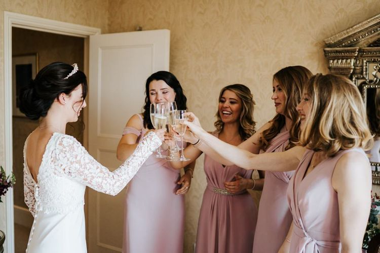 Bride and bridesmaids clinck glasses and cheer