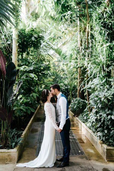 Bride and groom kiss and hold hands for Palm House at Kew Gardens wedding venue