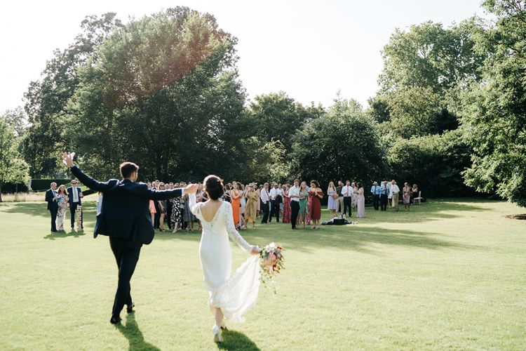 Guests enjoy drinks on the lawn at summer Kew Gardens wedding