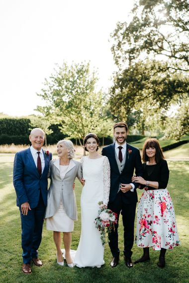 Bride and groom with family at summer wedding
