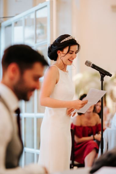 Bride stands and smiles as she delivers her wedding speech