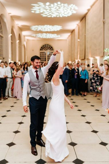 Bride and groom have their first dance as guests look on