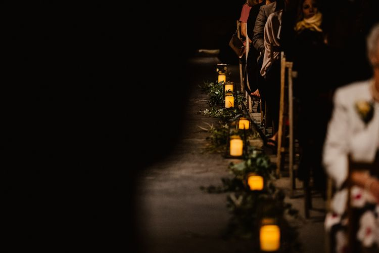Candles and Foliage Lining Aisle | The Electrician's Shop at Trinity Buoy Wharf | String Lights, Perspex Table Signs and Paper Cranes for Industrial Wedding | Frankee Victoria Photography