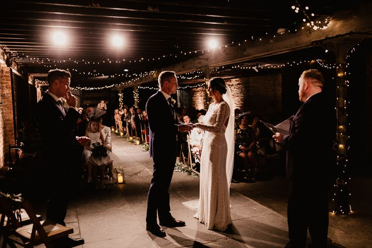 Bride in Lenora Dress by Wtoo Watters with Lace Sleeves and Keyhole Back | Prudence Halo Headpiece by Kelly Spence Wed | Floor Length Veil | Groom in Navy Suit with Grey Waistcoat from Jack Bunneys | Fairy Light Décor | Candle and Foliage Lined Aisle | Exposed Brick Industrial Venue | The Electrician's Shop at Trinity Buoy Wharf | String Lights, Perspex Table Signs and Paper Cranes for Industrial Wedding | Frankee Victoria Photography