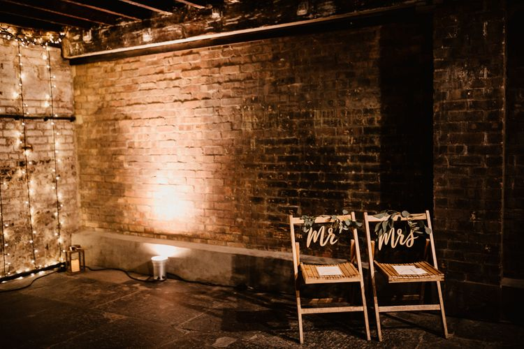 Wooden Chairs with Mr and Mrs Signs | Fairy Light Canopy | Exposed Brick Industrial Venue | The Electrician's Shop at Trinity Buoy Wharf | String Lights, Perspex Table Signs and Paper Cranes for Industrial Wedding | Frankee Victoria Photography