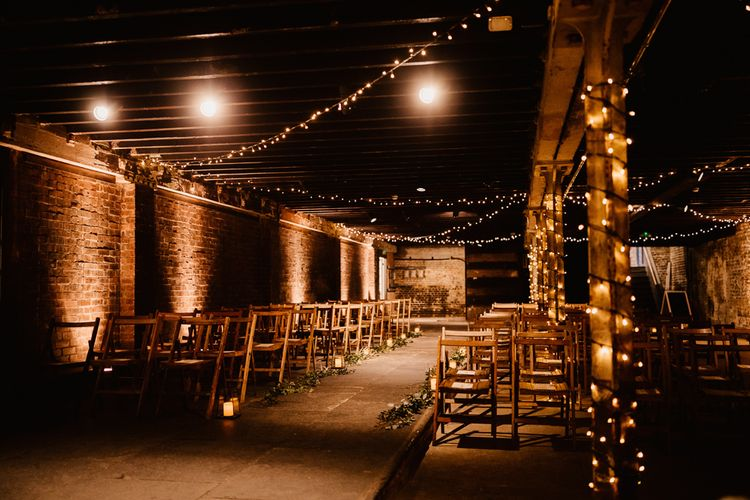 Fairy Light Décor | Candle and Foliage Lined Aisle | Exposed Brick Industrial Venue | The Electrician's Shop at Trinity Buoy Wharf | String Lights, Perspex Table Signs and Paper Cranes for Industrial Wedding | Frankee Victoria Photography