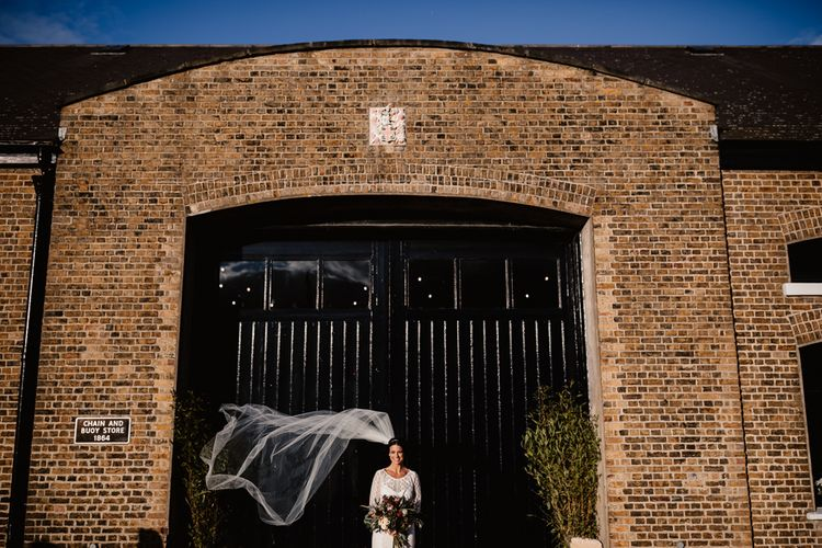 Bride in Lenora Dress by Wtoo Watters with Lace Sleeves and Keyhole Back | Prudence Halo Headpiece by Kelly Spence Wed | Floor Length Veil | String Lights, Perspex Table Signs and Paper Cranes for Industrial Wedding | Frankee Victoria Photography