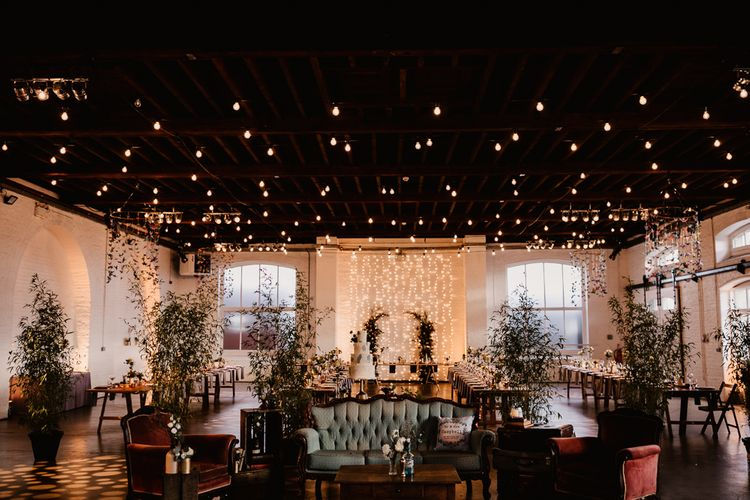 Festoon Lights | Hanging Paper Cranes | Vintage Sofas | Wooden Trestle Tables | Indoor Trees | Trinity Buoy Wharf Wedding Venue | String Lights, Perspex Table Signs and Paper Cranes for Industrial Wedding | Frankee Victoria Photography