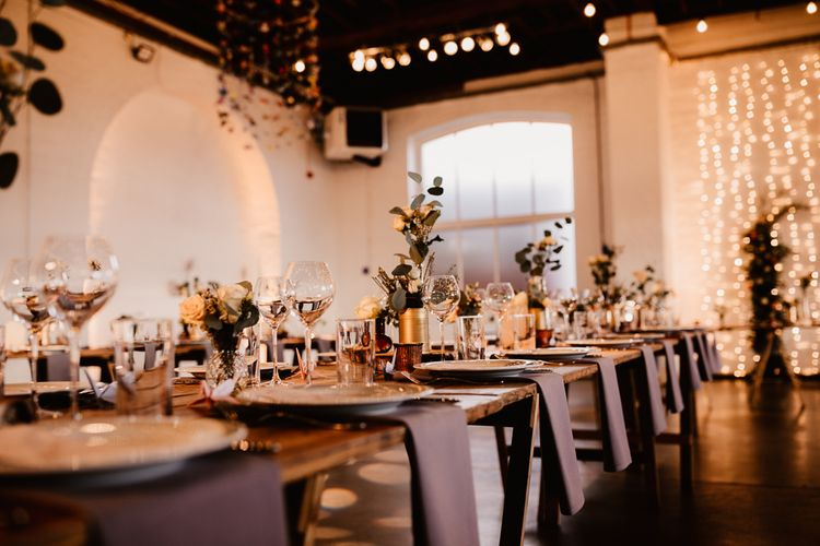 Wooden Trestle Tables | Grey Napkins | Festoon Lights | Hanging Paper Cranes | Flowers and Foliage in Gold Tin Cans | Paper Crane Place Settings | Trinity Buoy Wharf Wedding Venue | String Lights, Perspex Table Signs and Paper Cranes for Industrial Wedding | Frankee Victoria Photography