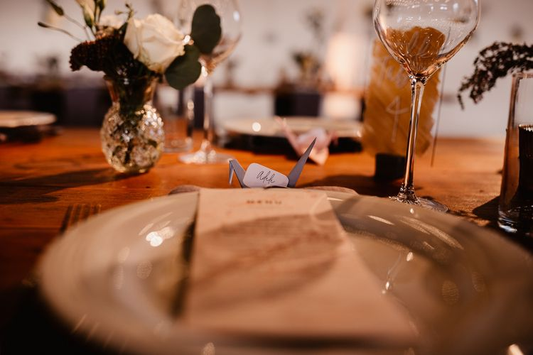 Paper Crane Place Settings | Copper and Perspex Table Sign | Flowers and Foliage in Bud Vase | Wedding Breakfast Menu | Trinity Buoy Wharf Wedding Venue | String Lights, Perspex Table Signs and Paper Cranes for Industrial Wedding | Frankee Victoria Photography