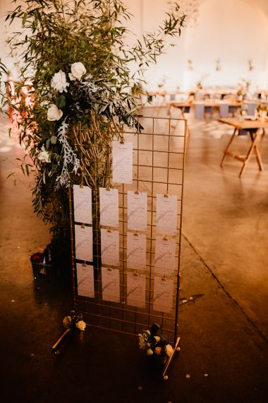 Copper Grid Table Plan | Foliage and White Flowers | Trinity Buoy Wharf Wedding Venue | String Lights, Perspex Table Signs and Paper Cranes for Industrial Wedding | Frankee Victoria Photography