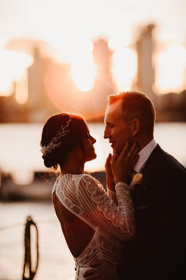 Bride in Lenora Dress by Wtoo Watters with Lace Sleeves and Keyhole Back | Prudence Halo Headpiece by Kelly Spence Wed | Groom in Navy Suit with Grey Waistcoat from Jack Bunneys | String Lights, Perspex Table Signs and Paper Cranes for Industrial Wedding | Frankee Victoria Photography