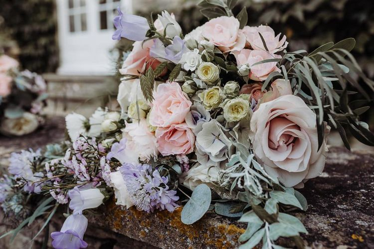 Pastel floral bridal bouquet at rustic barn wedding made up of roses and eucalyptus
