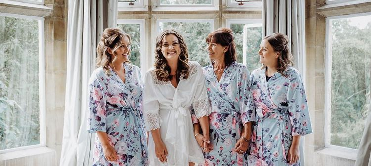 Bride and her bridesmaids getting ready wearing lace and floral kimonos for rustic wedding with pastel floral decor