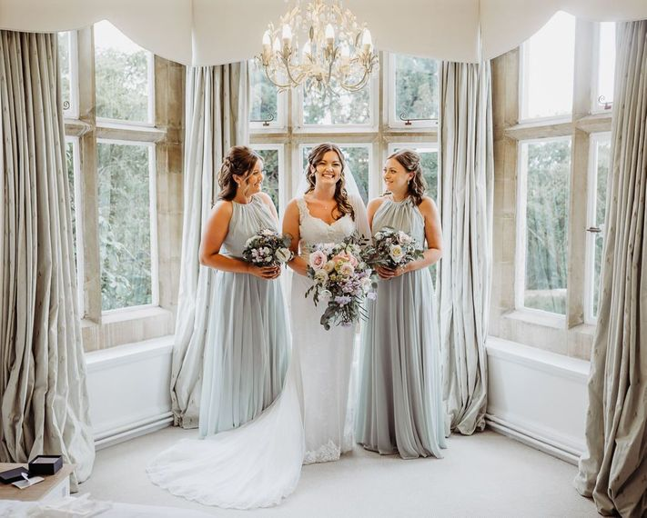 Bride and her bridesmaids clutching pastel floral bouquets at Cogges Manor Farm wedding