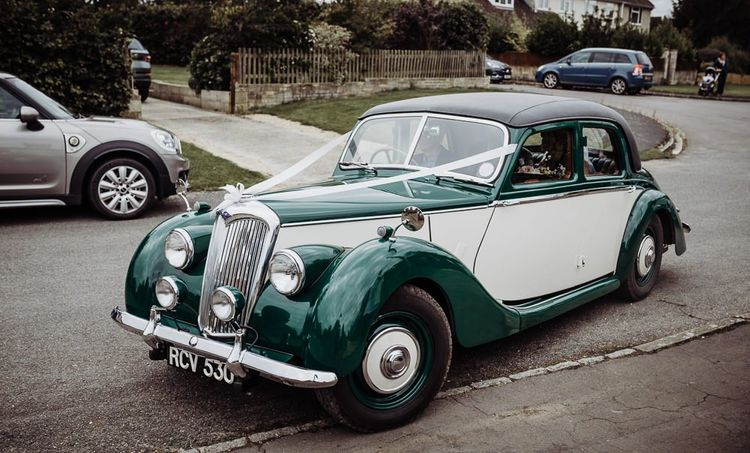 Vintage wedding car at Cogges Manor Farm celebration with rustic styling and floral decor