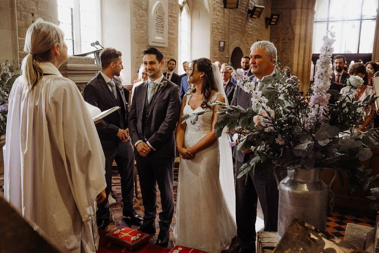 Bride and groom tie the knot at an intimate church wedding with pastel floral decoration before travelling to barn reception