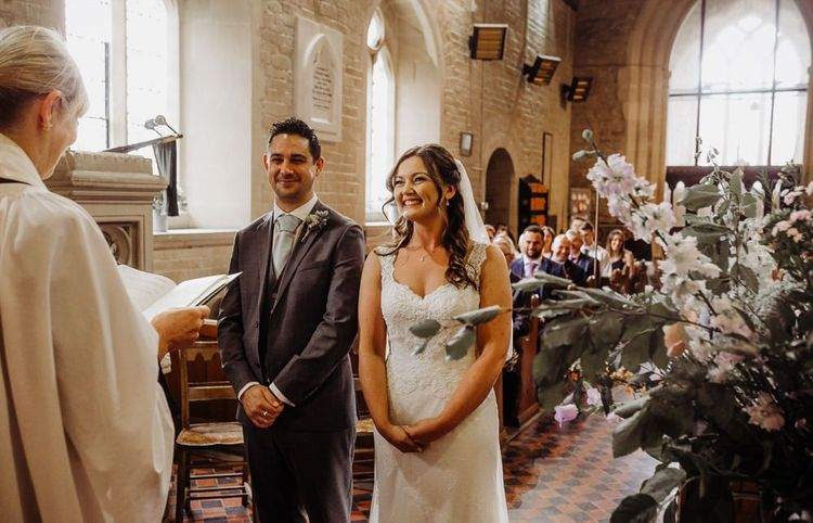Church wedding ceremony with pastel floral decor and a beautiful laced bridal dress
